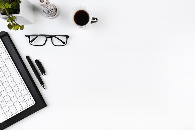 Lugar de trabajo de oficina con teclado y gafas