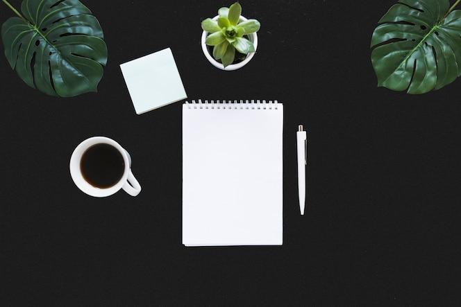 Lugar de trabajo ordenado con libreta y café