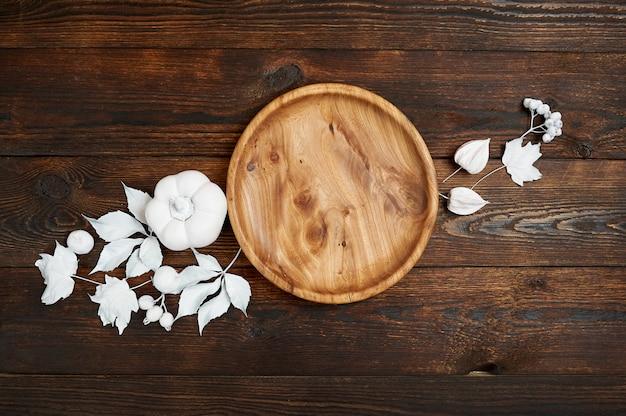 Lugar de madera con las bayas y las hojas blancas en una mofa de madera encima del fondo del otoño.