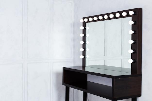 Lugar de maquillaje para mujer con espejo y bombillas.