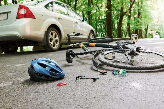 Lugar de peligro. bicicleta y accidente de coche de color plateado en la carretera en el bosque durante el día