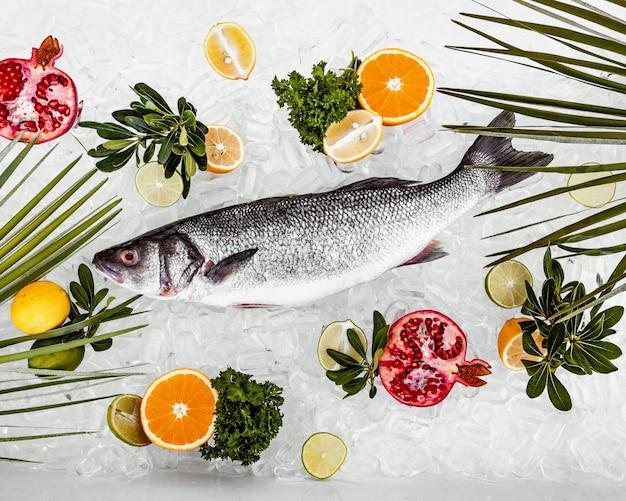 Lugar de pescado crudo en hielo rodeado de rodajas de frutas