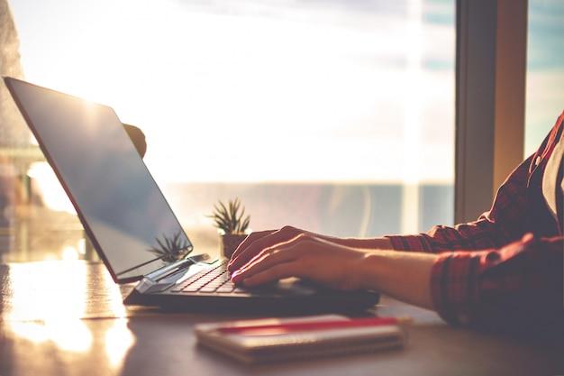 Lugar de trabajo acogedor en la oficina en casa con el portátil en la mesa contra las ventanas al atardecer para negocios en línea