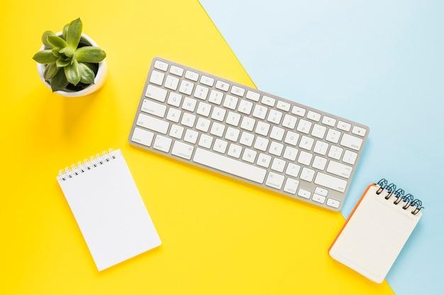 Lugar de trabajo acogedor con teclado y cuadernos