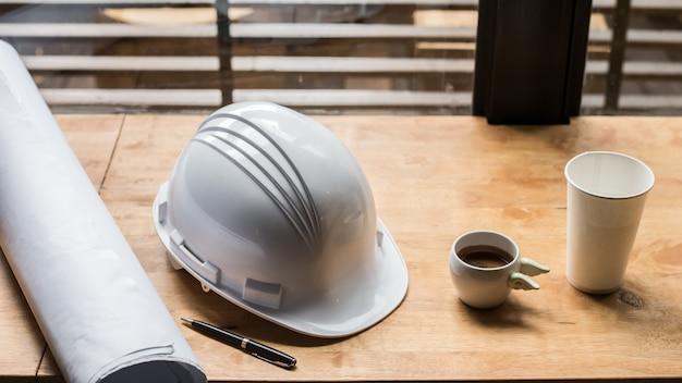 Lugar de trabajo del arquitecto - proyecto arquitectónico, planos, proyecto, taza de café. herramientas de ingeniería y gadgets desde la parte superior. fondo de la construcción. imagen tonificada caliente de la vendimia con la luz de la mañana.