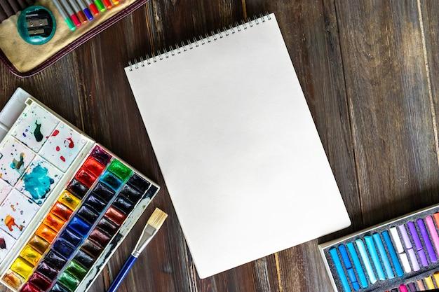 Lugar de trabajo de arte, lápices, pinceles, pinturas de acuarela, tizas de papel y crayones.