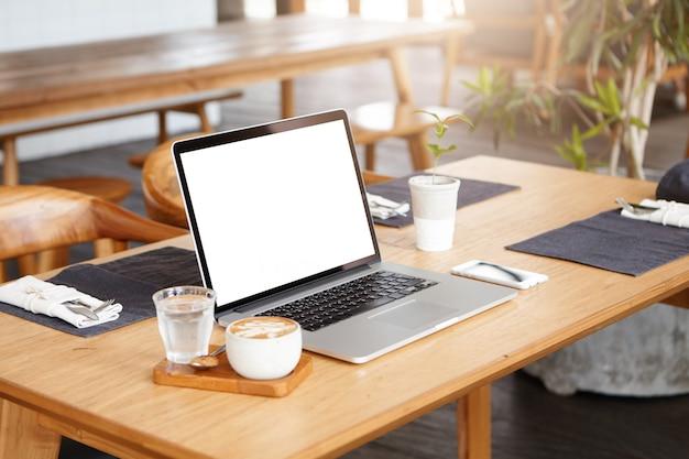 Lugar de trabajo de un autónomo desconocido cuando no hay nadie cerca: toma minimalista de una taza de café, un vaso de agua, un teléfono celular y una computadora portátil genérica