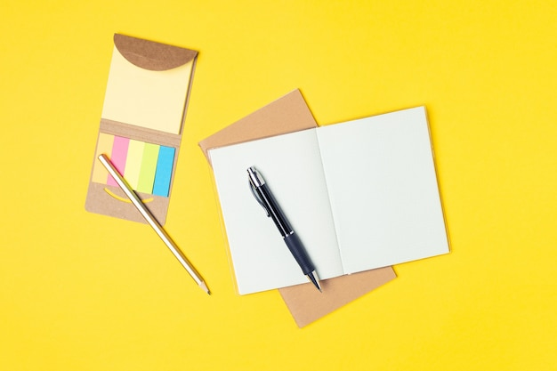 Lugar de trabajo, bloc de notas, notas adhesivas y bolígrafo sobre amarillo brillante.