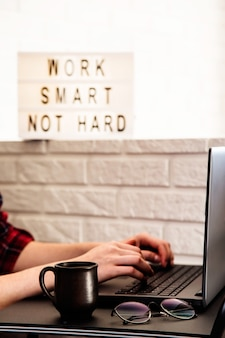 Lugar de trabajo en casa de un profesional independiente en una mesa con estilo negro cerca del sofá y la pared de ladrillo