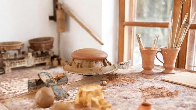 Lugar de trabajo de cerámica con diferentes creaciones en la mesa.