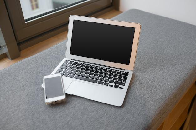 Lugar de trabajo cerca de la ventana con computadora portátil y computadora, espacio de copia