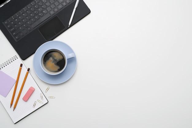 Lugar de trabajo con computadora portátil, café y bloc de notas, vista superior, copyspace