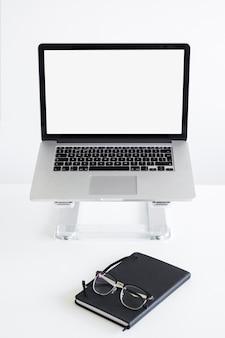 Lugar de trabajo con la computadora portátil en el stand cerca de anteojos y bloc de notas