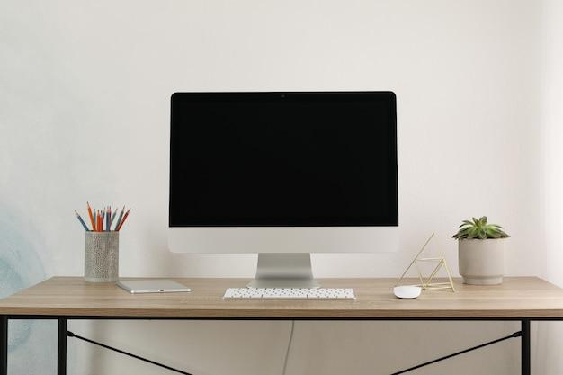 Lugar de trabajo con computadora, tableta y planta en mesa de madera, espacio para texto