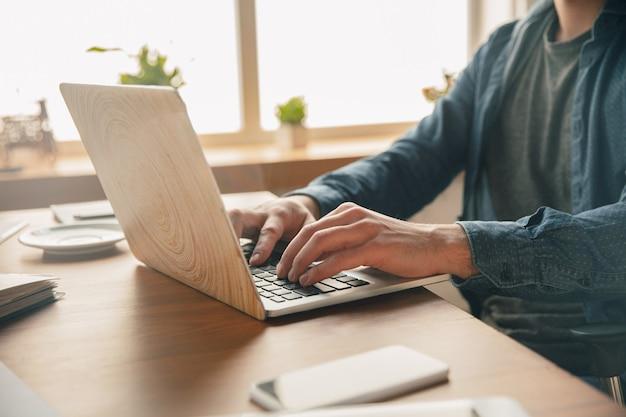 Lugar de trabajo creativo: espacio de trabajo organizado a su gusto para inspirarse. hombre que trabaja en la oficina con ropa cómoda, posición relajada y mesa desordenada. elija la atmósfera que desee: ideal claro o caos.
