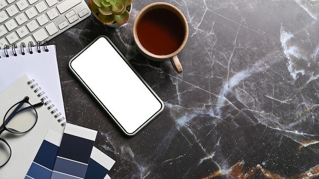Lugar de trabajo creativo con teléfono inteligente, taza de café, vasos y cuadernos en la mesa de mármol.