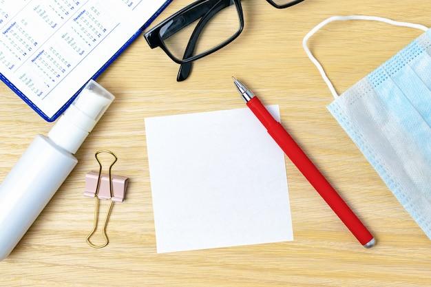 Lugar de trabajo en cuarentena de coronavirus. etiqueta engomada de papel blanco en blanco y bolígrafo rojo, máscara médica, desinfectante, gafas y un calendario en el escritorio de la oficina. trabajo remoto desde casa. hoja adhesiva para nota, planificación.