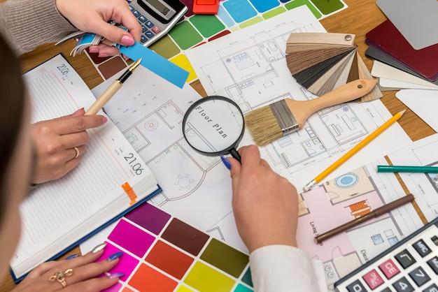 Lugar de trabajo de diseñadores creativos con paleta de colores y proyecto de casa.