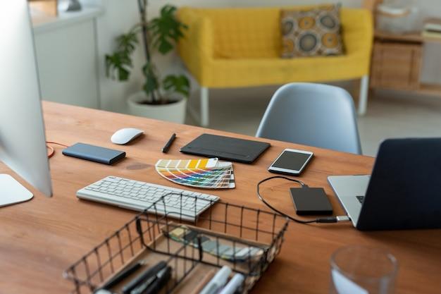 Lugar de trabajo de diseñadores gráficos con muestra de color, digitalizador, teléfono inteligente y computadoras en la oficina en casa