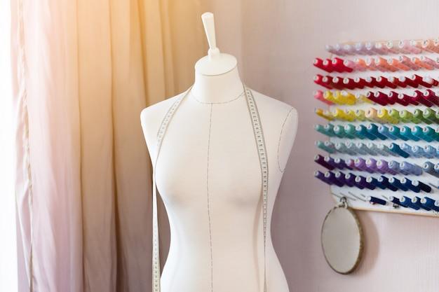 Lugar de trabajo de diseño con coser maniquíes, bobinas con hilos y cinta métrica.