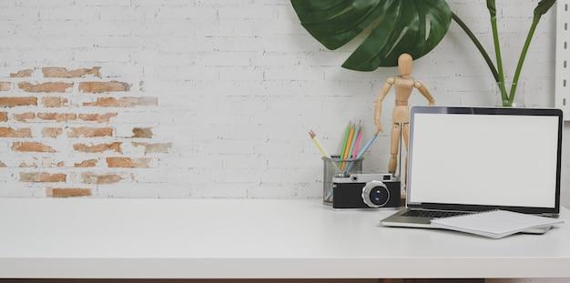 Lugar de trabajo de diseño minimalista con cámara y material de oficina en mesa blanca