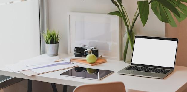 Lugar de trabajo de diseño moderno con computadora portátil de pantalla en blanco