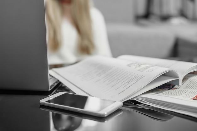 Lugar de trabajo. la educación a distancia. ordenador portátil, teléfono móvil, cuaderno sobre la mesa y silueta borrosa de una joven estudiante en el fondo del sofá