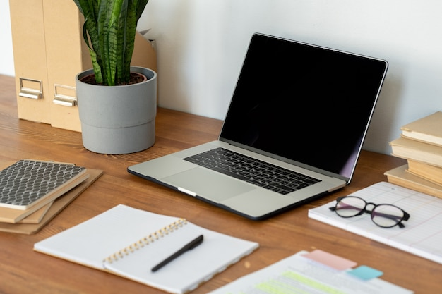 Lugar de trabajo del empleado de la oficina en casa con computadora portátil, anteojos, cuaderno abierto con lápiz y otros suministros en la mesa de madera