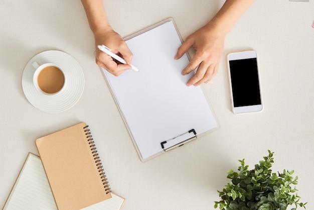 Lugar de trabajo de escritor, reescritor. mano femenina sosteniendo la pluma y escribiendo en el bloc de notas. concepto de planificación empresarial y lluvia de ideas