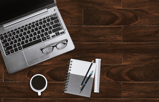 Lugar de trabajo de escritorio de oficina en casa con laptop con lentes y cuaderno con espacio de copia.