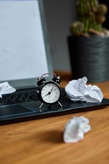 Lugar de trabajo, escritorio de oficina de madera con reloj, hoja de papel, computadora portátil, cuaderno, bolas de papel arrugadas y suministros, cambie su mentalidad, plan b, tiempo para establecer nuevas metas, planes, concepto de gestión del tiempo.