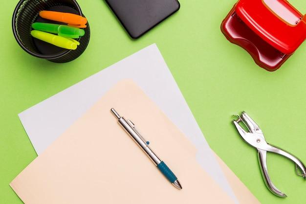 Lugar de trabajo de escritorio verde con herramientas de oficina.