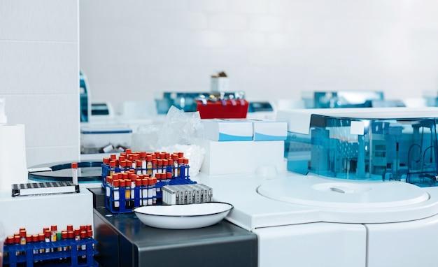 Lugar de trabajo estéril. grandes soportes para tubos de ensayo con sangre en cada mesa, el laboratorio es muy conveniente y limpio