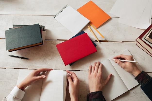 Lugar de trabajo de estudiar a los alumnos con suministros. vista superior en el escritorio con cuadernos y manos de estudiantes, escribiendo en él.