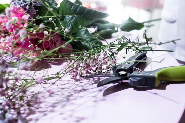 El lugar de trabajo de la florería es una mesa con flores y una podadora.