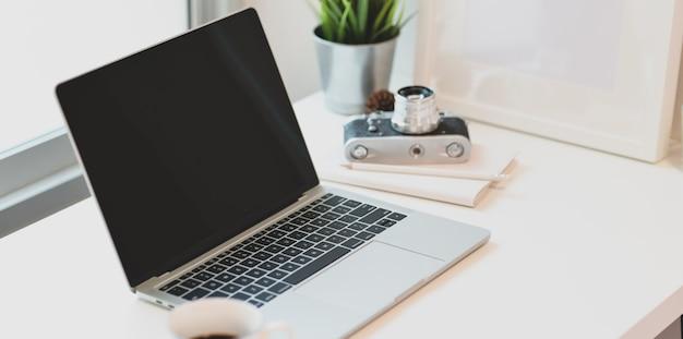 Lugar de trabajo del fotógrafo moderno con computadora portátil abierta