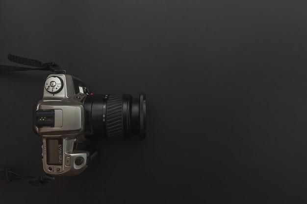 Lugar de trabajo del fotógrafo con sistema de cámara réflex digital y accesorio de cámara sobre fondo negro oscuro