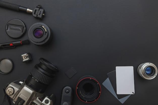 Lugar de trabajo de fotógrafo con sistema de cámara réflex digital, kit de limpieza de cámara, lente y accesorio de cámara sobre fondo de mesa negro oscuro