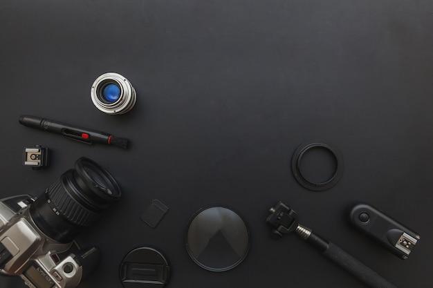 Lugar de trabajo de fotógrafo con sistema de cámara réflex digital, kit de limpieza de cámara, lente y accesorio de cámara