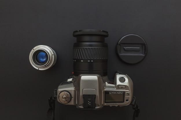 Lugar de trabajo del fotógrafo con sistema de cámara réflex digital y lente en mesa negro oscuro