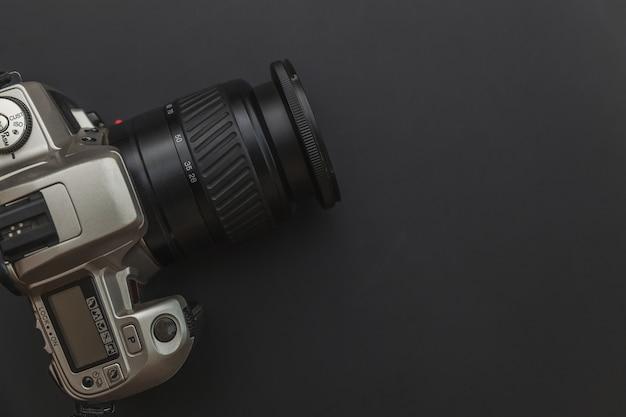 Lugar de trabajo de fotógrafo con sistema de cámara réflex digital en mesa negro oscuro