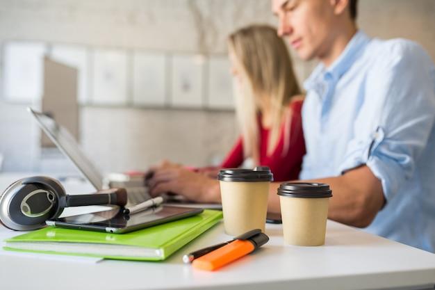 Lugar de trabajo fresco de personas que trabajan juntas en la oficina de trabajo conjunto en la computadora portátil