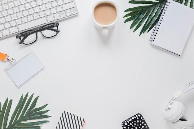 Lugar de trabajo con gadgets, taza de café y vasos cerca de palmeras.