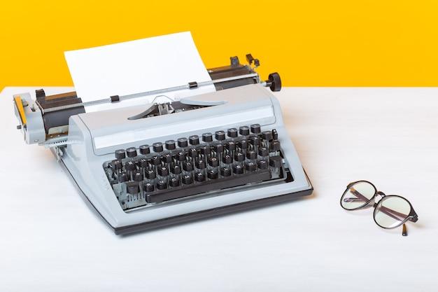 El lugar de trabajo del gerente de la secretaria y la máquina de escribir de negocios y los vasos están sobre la mesa