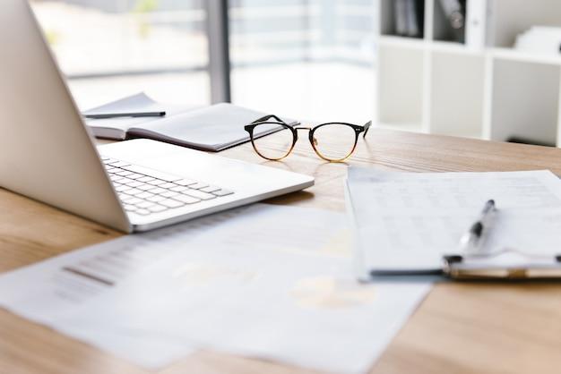 Lugar de trabajo en la habitación de la oficina sin gente con computadora portátil abierta, portapapeles, gafas, lápiz y cuaderno sobre un escritorio de madera