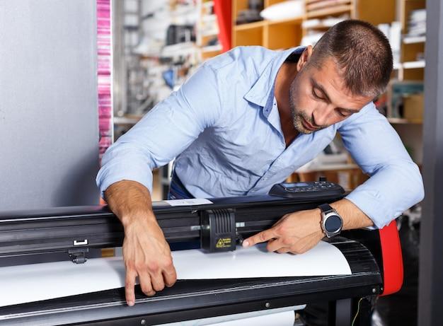 Lugar de trabajo de impresión de papel de trabajador masculino
