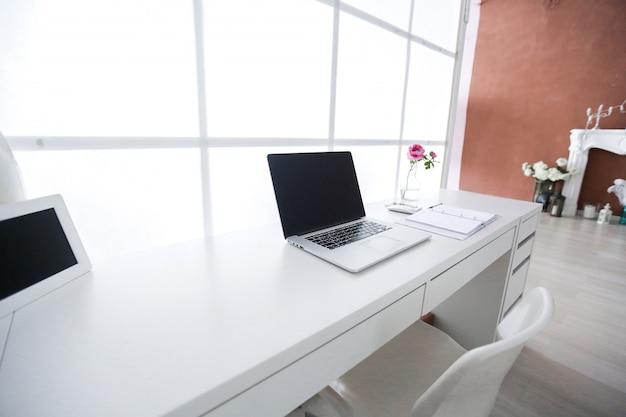 Lugar de trabajo interior moderno con ordenador portátil en colores blancos.