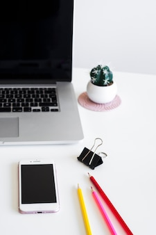 Lugar de trabajo con laptop cerca de lápices, clip y teléfono inteligente.