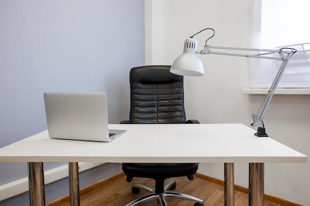Lugar de trabajo con laptop y lámpara.