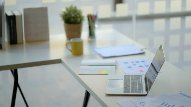 Lugar de trabajo con laptop, material de oficina y café.